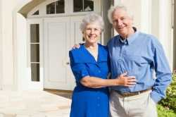 matured retired couple standing in front of their home