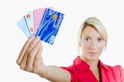 girl holding and showing credit cards in her hands