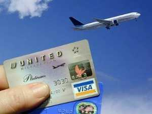 Holding two credit card with an aeroplane in the background